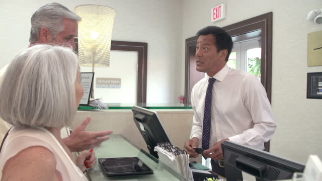 Senior Couple Checking In At Hotel Reception video