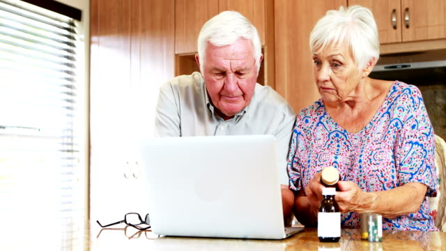 Senior couple checking medicine while using laptop in kitchen video