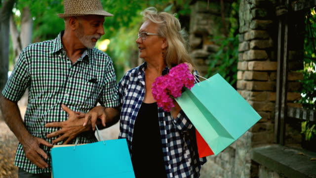 Senior couple coming back from shopping. video