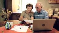 Senior couple doing home finance video