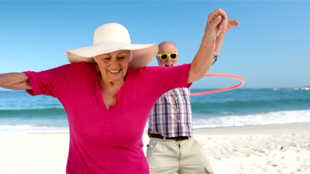 Senior couple doing hula hoop video