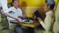 Senior couple eating at restaurant video