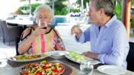Senior Couple Enjoying Meal In Outdoor Restaurant video