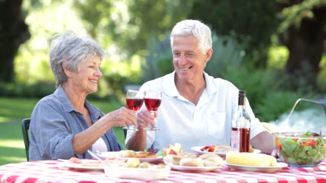 Senior Couple Enjoying Summer Barbeque In Garden video
