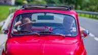Senior couple enjoying the conversation in a red zastava car video