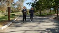 Senior Couple Exercising With Run Through Park video