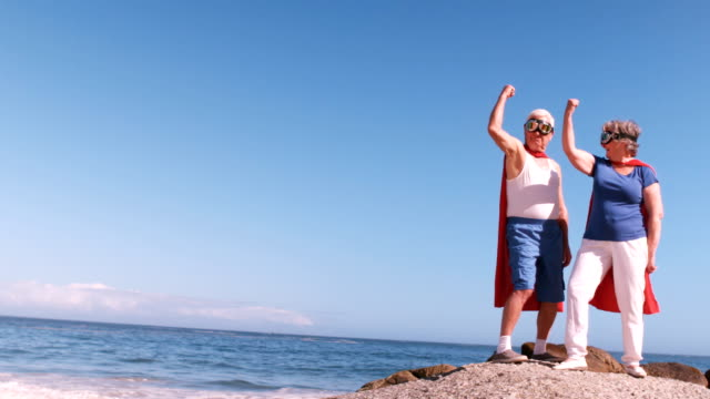senior couple flexing arms on the beach video
