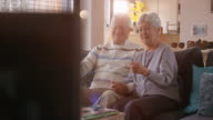 Senior couple having a good time watching TV video