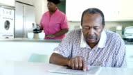 Senior Couple Having Breakfast As Husband Reads Newspaper video