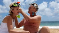 Senior couple helping each other with snorkel gear video