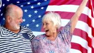 Senior couple holding american flag video