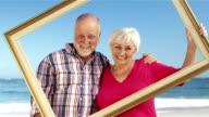 Senior couple holding frame video