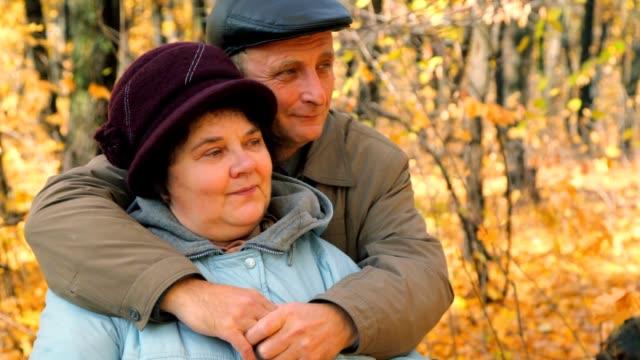 Senior couple hugging against trees in autumn park video