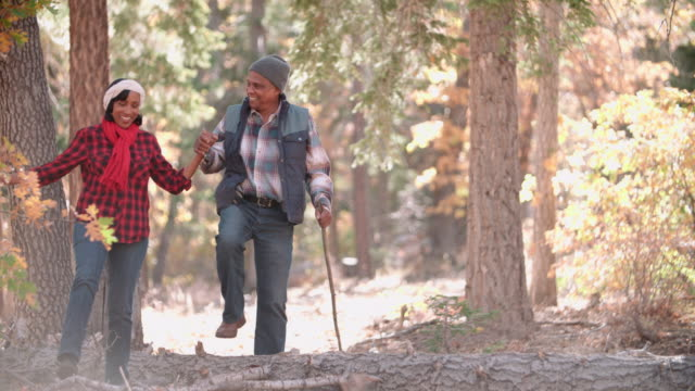Senior couple in a forest walk to camera, on left of frame video