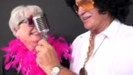 Senior couple in costumes singing and having fun video