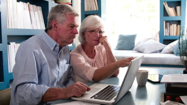 Senior Couple In Home Office Looking At Laptop video