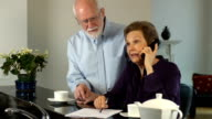 Senior Couple Interact on Telephone. video