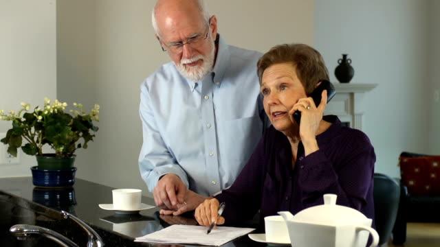 Senior Couple Interact on Telephone. video