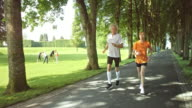 SLO MO TS Senior couple jogging through a park video
