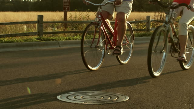 Senior couple joyfully ride bikes together. video