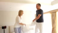 Senior Couple Jumping On Bed Having Pillow Fight Together video