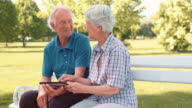Senior couple laughing while using a tablet in the park video
