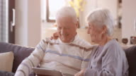 Senior couple laughing while watching something on digital tablet video