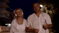 Senior couple listening to music during night walk video