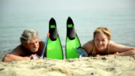 Senior couple on beach with diving equipment video