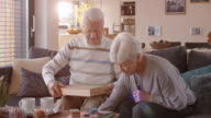 Senior couple on the sofa with a board game video