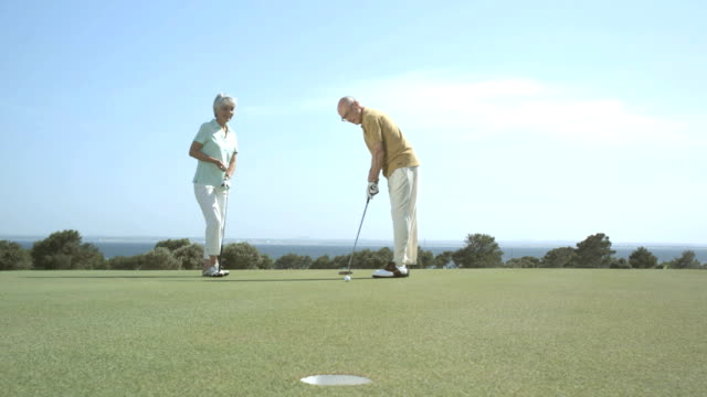 senior couple playing golf video