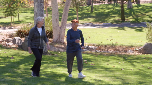 Senior Couple Power Walking Through Park In Slow Motion video