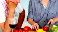 Senior couple preparing a healthy meal while drinking red wine video