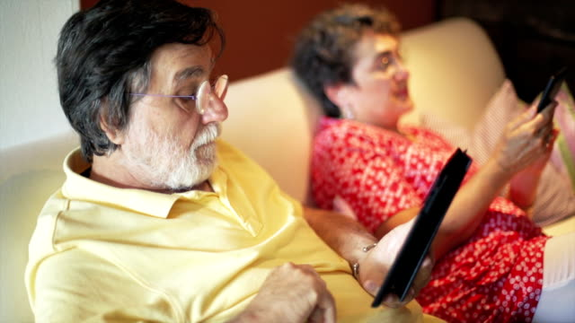 Senior couple relax on sofa using a digital tablet video