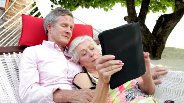 Senior Couple Relaxing In Beach Hammock Using Digital Tablet video