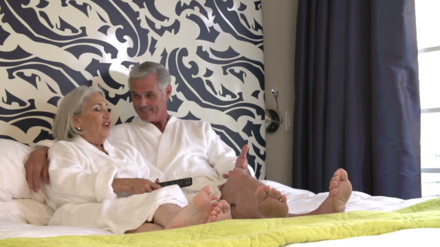 Senior Couple Relaxing In Hotel Room Watching Television video