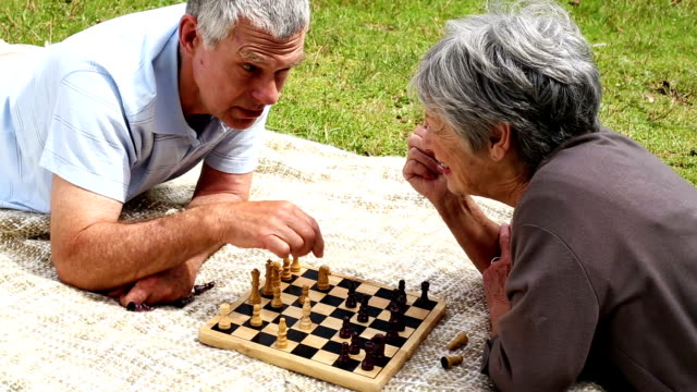 Senior couple relaxing in park lying on blanket playing chess video