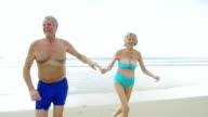 Senior couple running on beach holding hands video