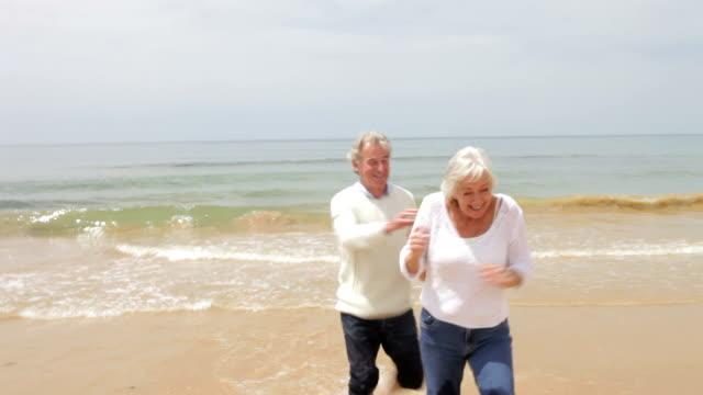 Senior Couple Running On Fall Beach video