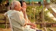 Senior couple sitting near river during sunset video