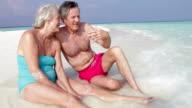 Senior Couple Sitting On Beautiful Beach video