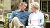 Senior couple sitting on patio sofa, talking, laughing video