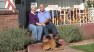 Senior couple sitting on porch with dog video