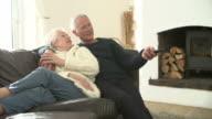 Senior Couple Sitting On Sofa Watching TV video