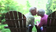 Senior Couple Sitting Outdoors in Adirondack Chairs video