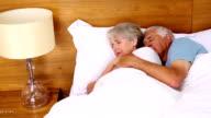 Senior couple sleeping in bed video