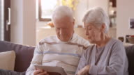 Senior couple smiling while watching something on digital tablet video