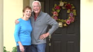 Senior couple standing together outside their home video