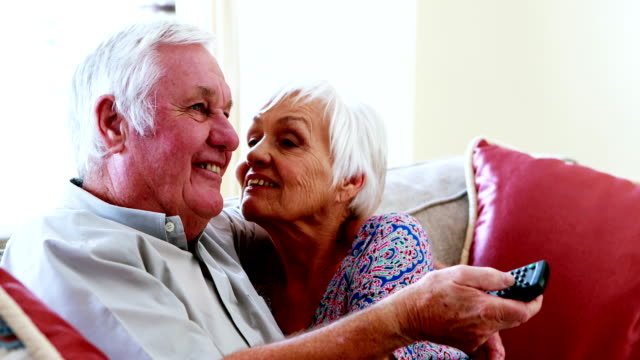 Senior couple talking while watching television in living room video