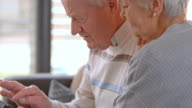 SLO MO Senior couple using a digital tablet video